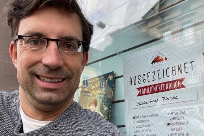 lächelnder Mann mit Urkunde von kinder willkommen vor Schaufenster einer Buchhandlung