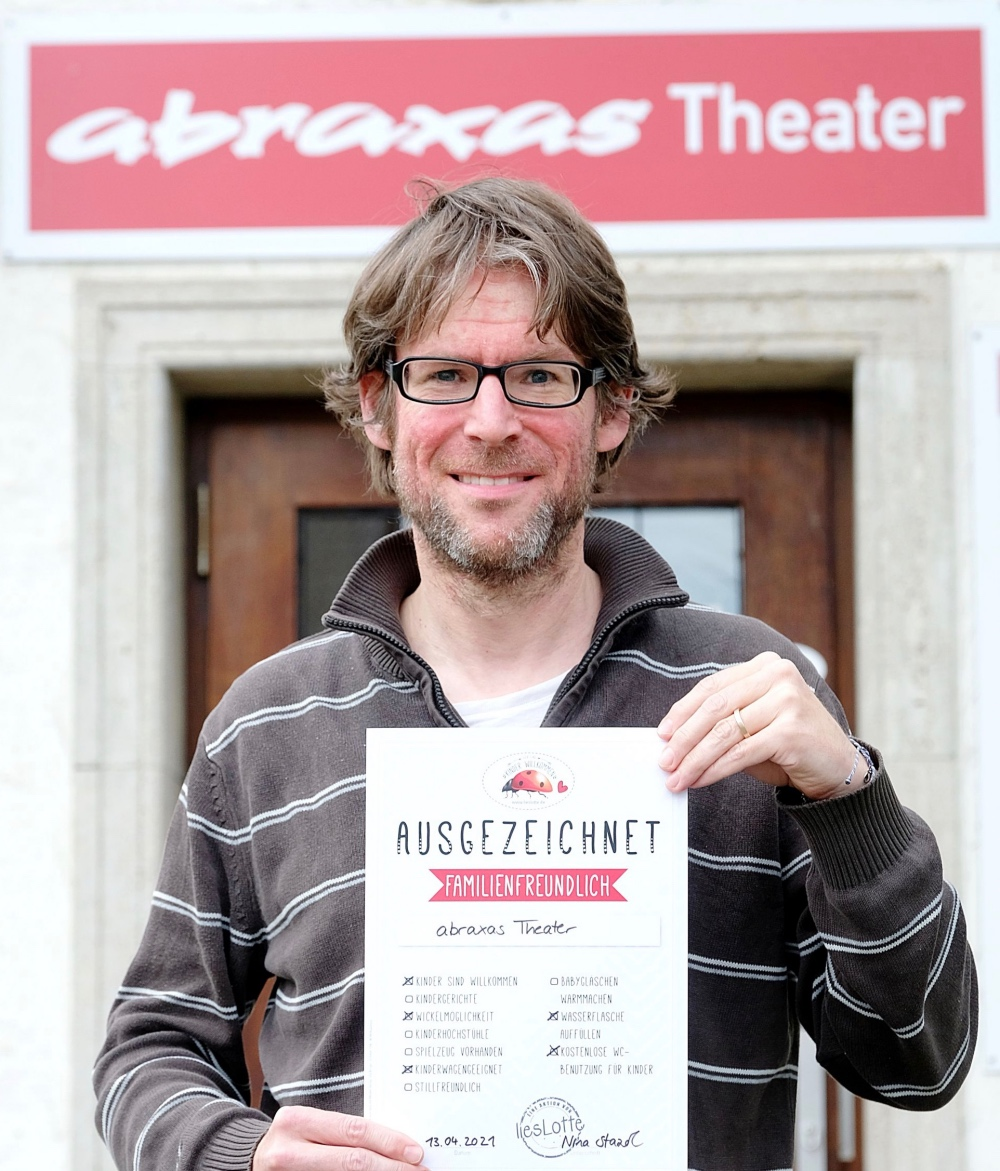 Mann hält Urkunde vor Theater abraxas Augsburg