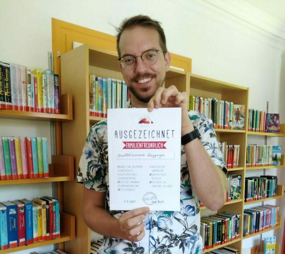 Mann mit Urkunde in Bücherei vor Buchregal, Göggingen