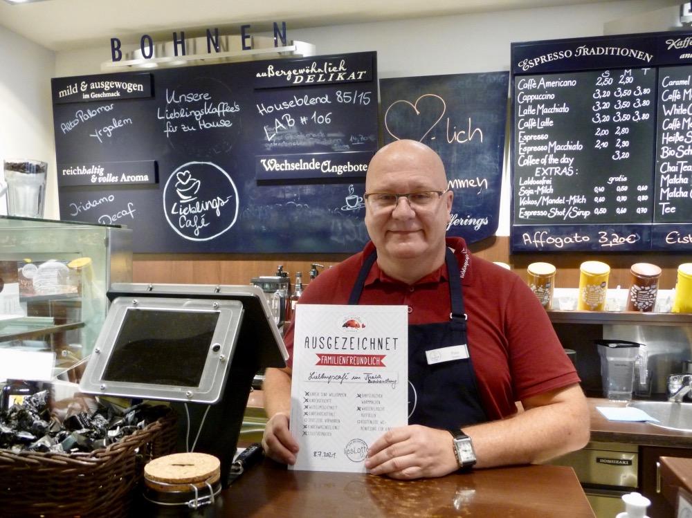 Mann mit Urkunde vor Ladentheke im Lieblingsafé