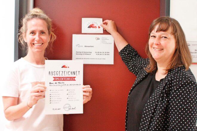 """zwei Mitarbieterinnen der AWO Schwaben halten Urkunde mit Auszeichnung """"familienfreundliches Augsburg"""" hoch, lächelnd"""